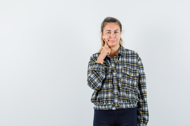 Young lady suffering from toothache in shirt, shorts and looking uncomfortable. front view.