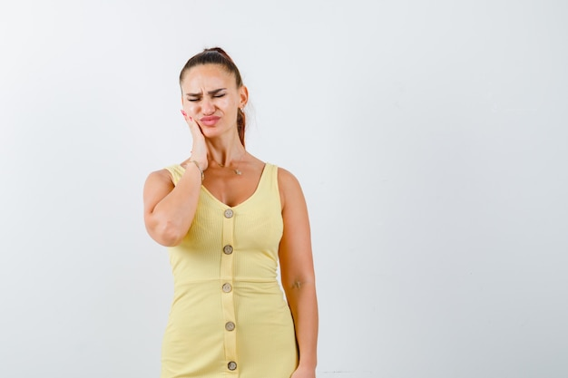 Young lady suffering from toothache in yellow dress and looking painful. front view.