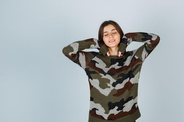 Молодая дама дуется щеками, опираясь на руки в свитере и выглядит мирно