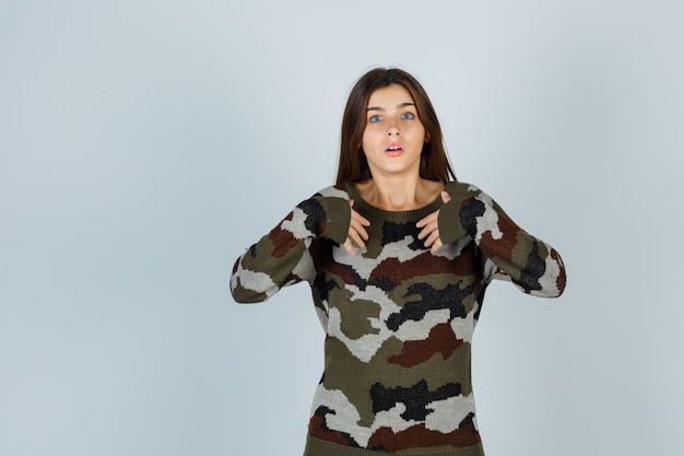 Young lady in sweater holding hands on chest as asking question and looking perplexed