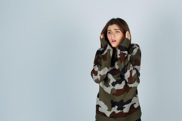 Giovane donna in maglione tenendo le mani vicino al viso e guardando ansioso