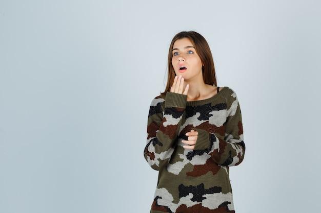 Giovane donna in maglione tenendo le mani vicino alla bocca e guardando perplesso
