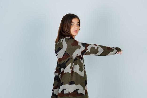 Giovane donna in maglione in posa mentre si gratta la mano e sembra fresca