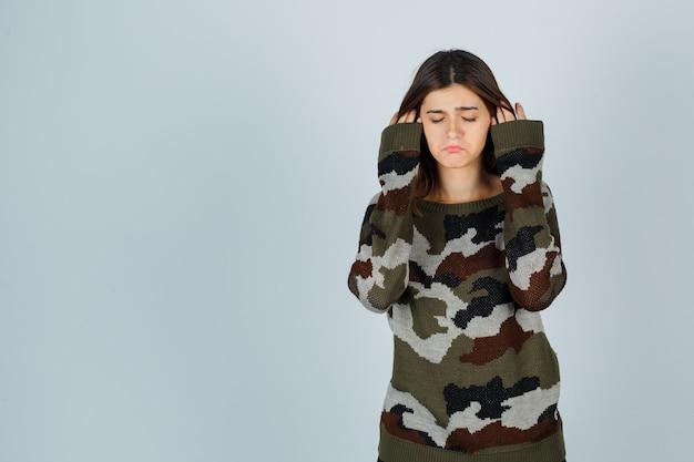 Giovane donna in maglione in posa mentre rimbocca i capelli e sembra delusa