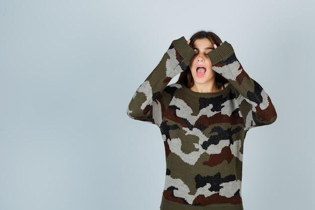 Giovane donna in maglione alzando le mani in gesto di resa e guardando divertito