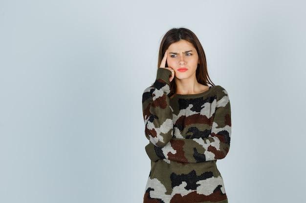Giovane donna in maglione, gonna tenendo il dito sulle tempie e guardando pensieroso