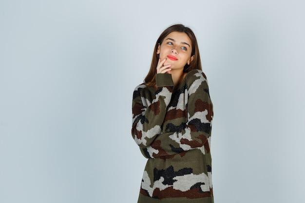 Giovane donna in maglione, gonna tenendo la mano sul mento e guardando allegra