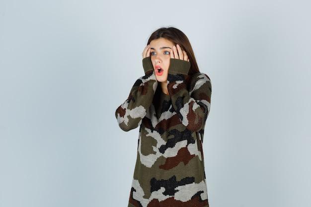 Giovane donna in maglione, gonna tenendo le mani sulle guance e guardando perplesso