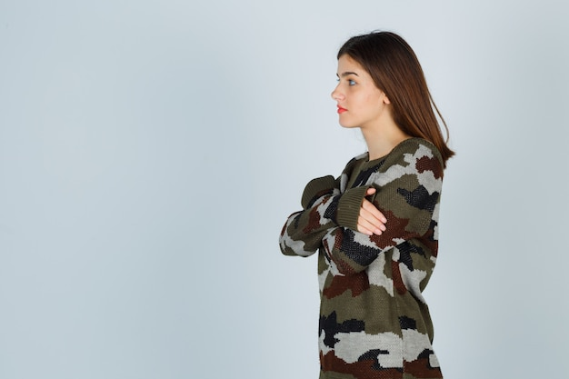Young lady in sweater, skirt hugging herself and looking pensive