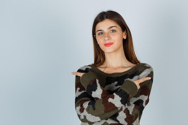Giovane donna in maglione, gonna che punta su entrambi i lati