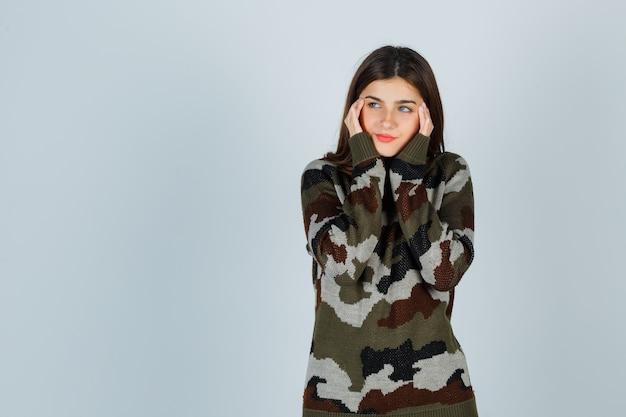 Giovane donna in maglione, gonna strofinando le tempie e guardando pensieroso