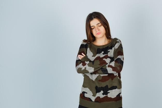 Giovane donna in maglione in piedi con le braccia incrociate e che sembra triste
