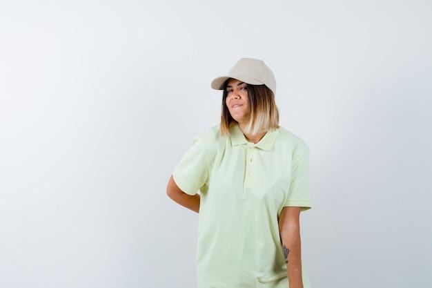 Giovane donna in t-shirt, berretto tenendo la mano dietro la schiena mentre posa e sembra carina, vista frontale.