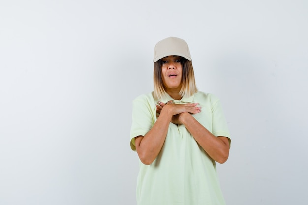 Young lady in t-shirt, cap holding hands on chest and looking puzzled , front view.