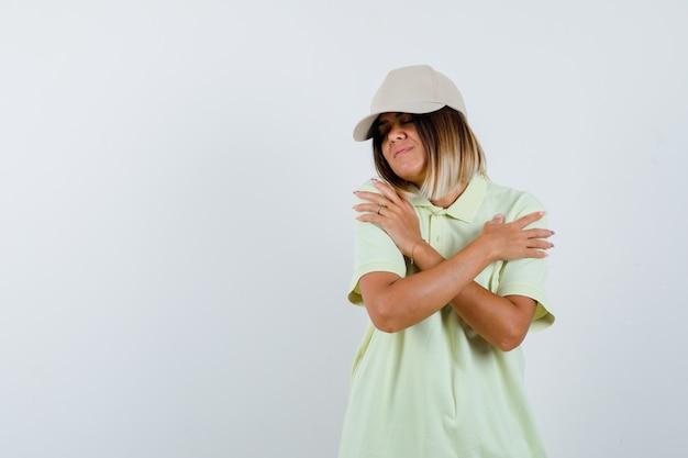 Giovane donna in t-shirt, berretto che si abbraccia e che sembra carina, vista frontale.