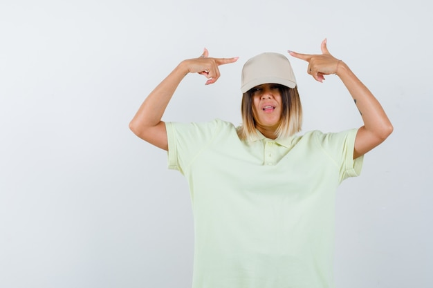 Young lady in t-shirt, cap pointing at both sides and looking confident , front view.