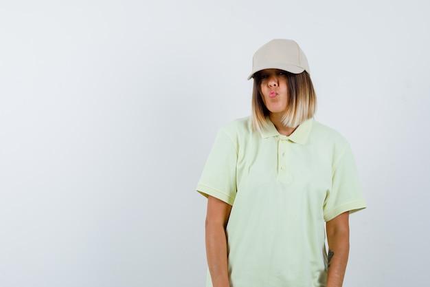 Giovane donna in t-shirt, berretto che invia un bacio mentre posa e sembra carina, vista frontale.