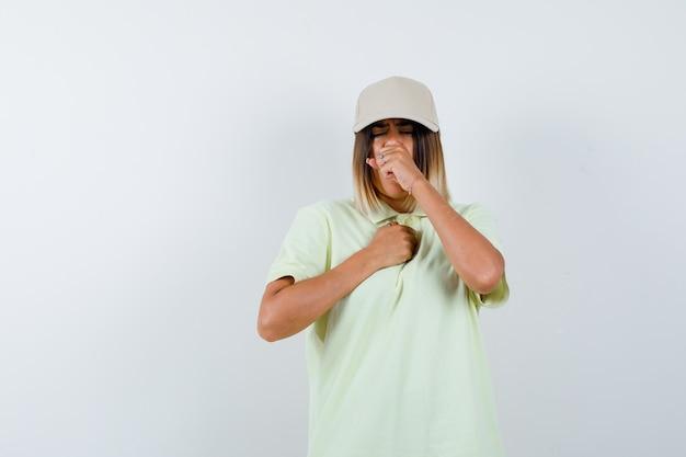Giovane donna in t-shirt, berretto che soffre di tosse e non si sente bene, vista frontale.