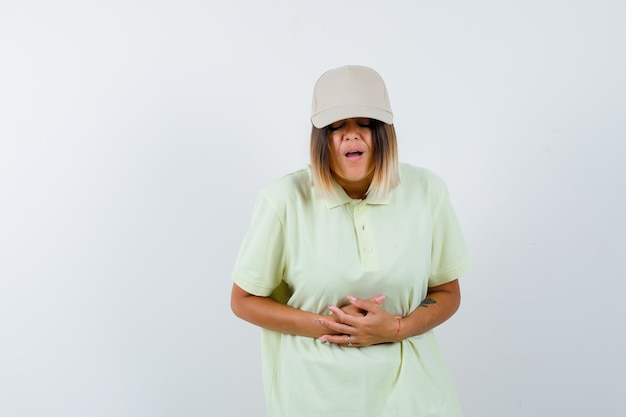 Young lady in t-shirt, cap suffering from stomach pain and looking sick , front view.