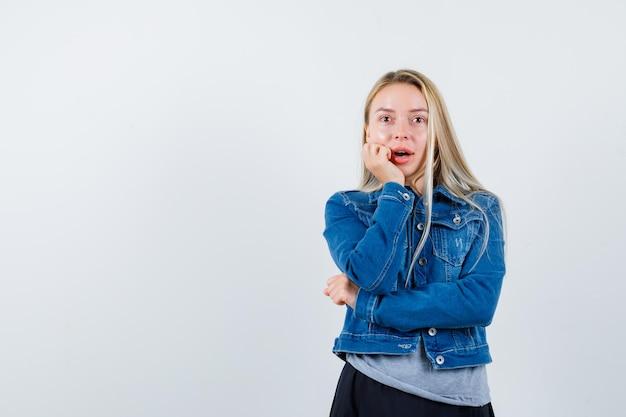 Giovane donna in t-shirt, giacca di jeans, gonna con il mento appoggiato sulla mano e con l'aria stupita