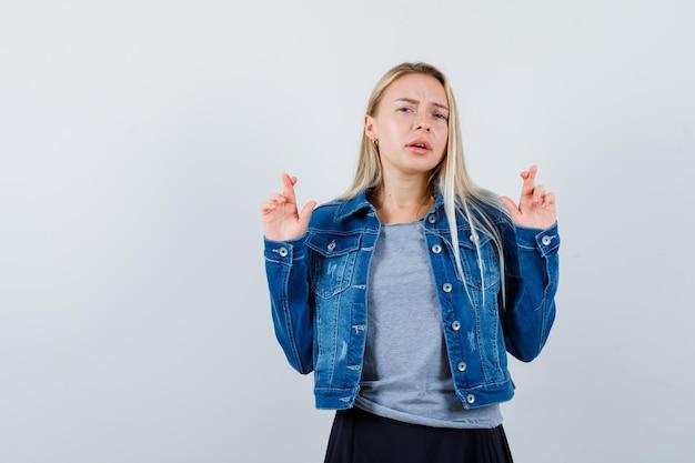 Giovane donna in t-shirt, giacca di jeans, gonna che mostra le dita incrociate e sembra carina