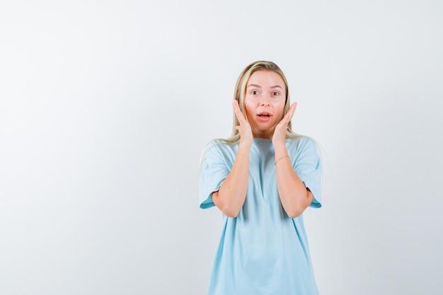 Giovane donna in t-shirt tenendo le mani vicino alle guance e guardando perplesso, vista frontale.
