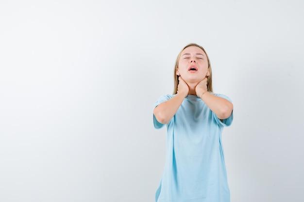 Giovane donna in maglietta che si tiene per mano sul collo e sembra stanca isolata