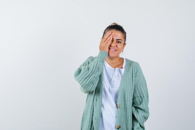 Giovane donna in t-shirt, giacca che copre gli occhi con la mano e sembra gioiosa