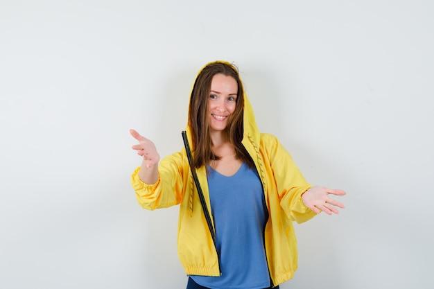 Giovane donna in maglietta, giacca che fa un gesto di benvenuto e sembra allegra