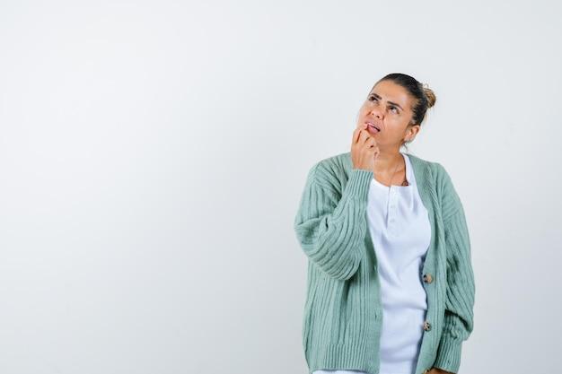 Giovane donna in maglietta, giacca che tiene il dito sulla bocca e sembra pensierosa