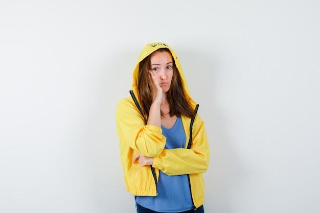 Giovane donna in maglietta, giacca che tiene la mano sulla guancia e sembra pensierosa