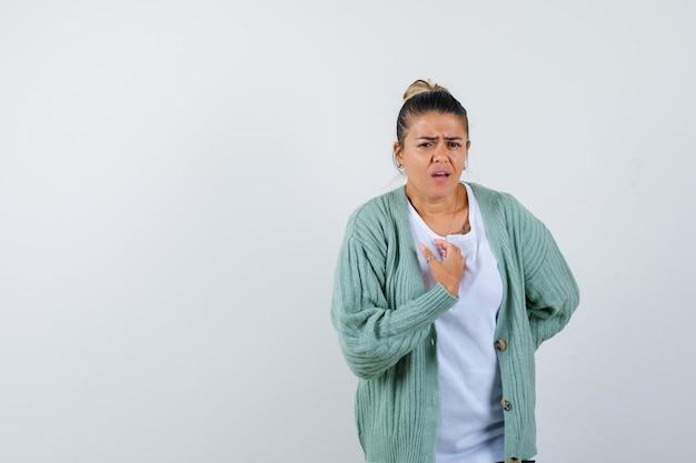 Giovane donna in t-shirt, giacca che tiene la mano sul petto e sembra malinconica