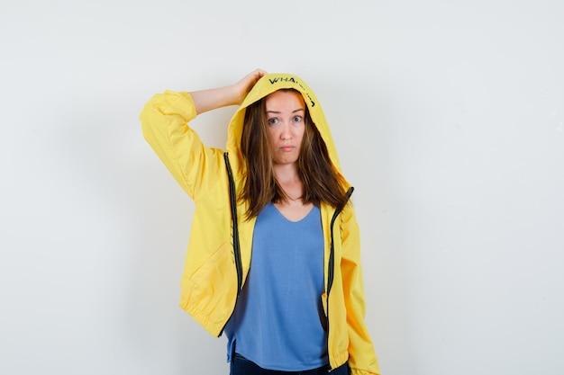 Giovane donna in maglietta, giacca che tiene la mano sulla testa e sembra perplessa