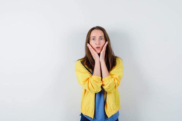 Giovane donna in t-shirt, giacca che si tiene per mano sulle guance e sembra sorpresa, vista frontale.