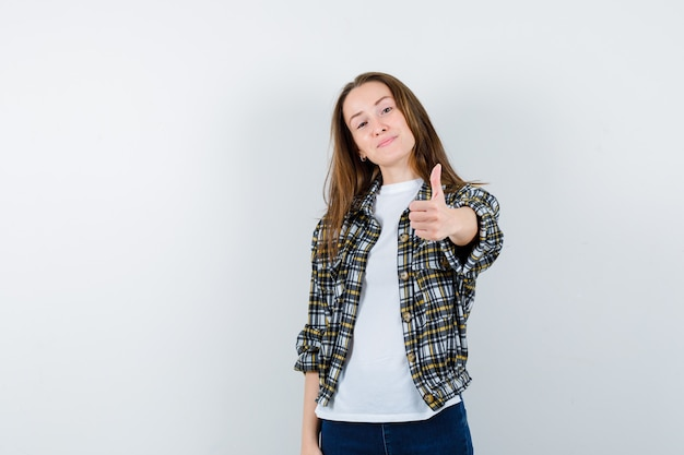 Young lady in t-shirt, jacket, jeans showing thumb up and looking confident , front view.