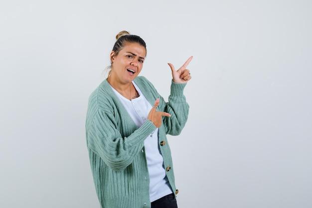 Giovane donna in t-shirt, giacca che punta da parte e sembra gioiosa