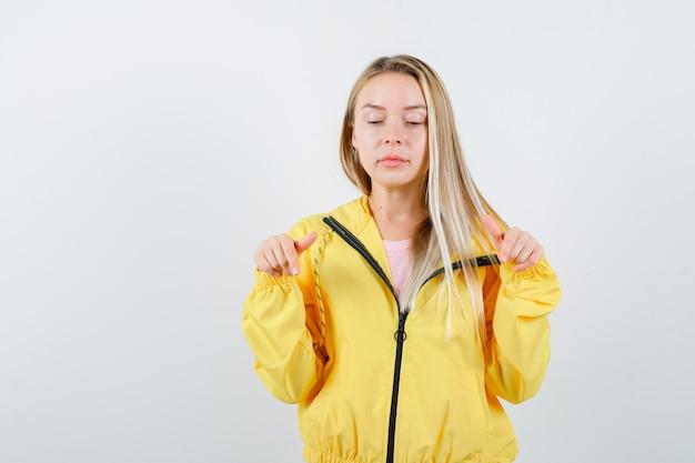 Giovane donna in t-shirt, giacca con la punta rivolta verso il basso e guardando fiducioso