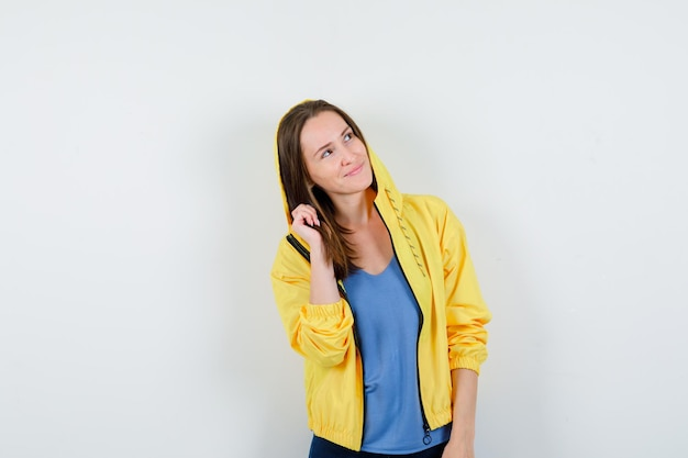 Young lady in t-shirt, jacket posing while looking up and looking dreamy