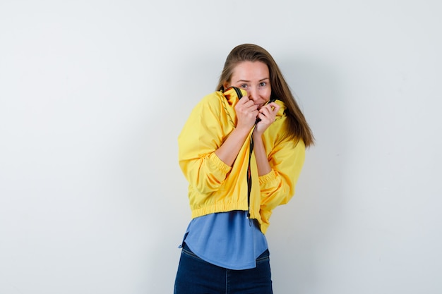 Young lady in t-shirt, jacket pulling collar on face and looking scared, front view.