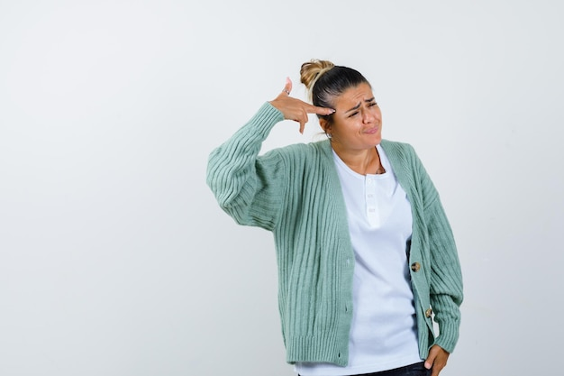 Young lady in t-shirt, jacket shooting herself with hand gun and looking hopeless