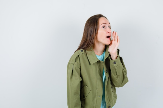 Young lady in t-shirt, jacket shouting something with hand and looking serious , front view.