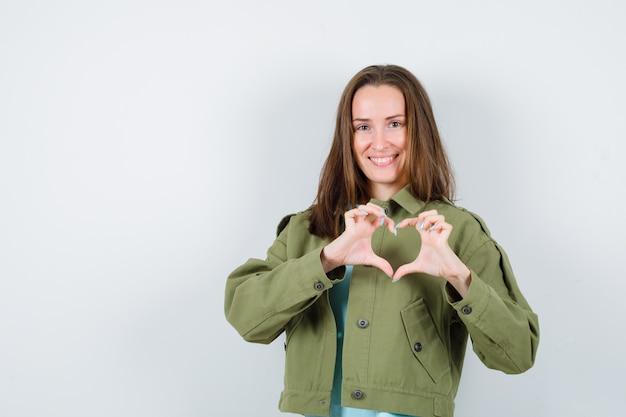 Giovane donna in t-shirt, giacca che mostra il gesto del cuore e sembra carina, vista frontale.