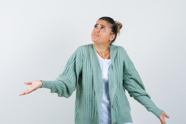 Giovane donna in maglietta, giacca che mostra un gesto impotente e sembra pensierosa