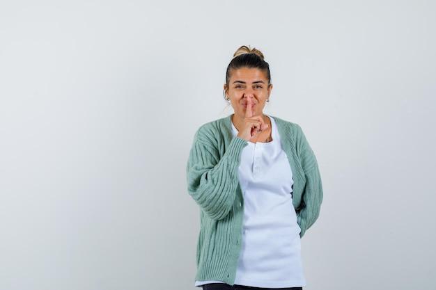 Giovane donna in t-shirt, giacca che mostra gesto di silenzio e sembra felice