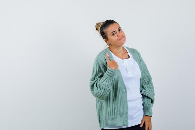 Giovane donna in t-shirt, giacca che mostra pollice in su e sembra sicura