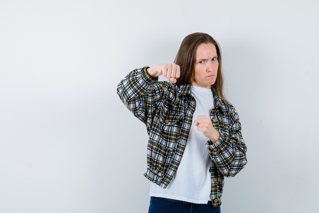 Giovane donna in t-shirt, giacca in piedi in posa di combattimento e guardando dispettoso, vista frontale.