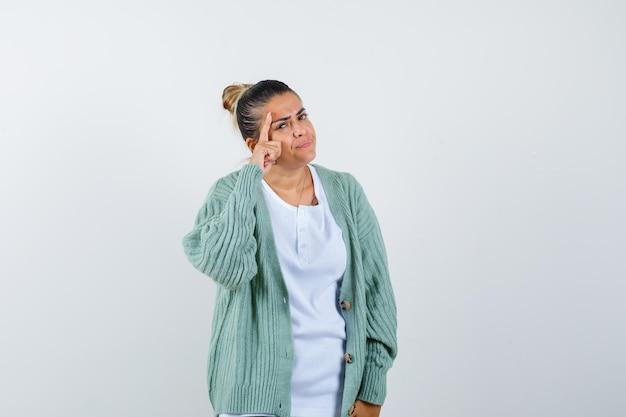 Giovane donna in maglietta, giacca in piedi in posa pensante e con aria pensierosa