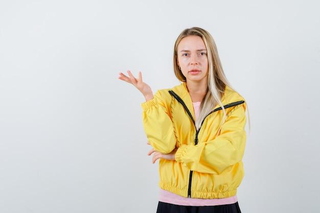 Giovane donna in t-shirt, giacca che allunga la mano nel gesto interrogativo e che sembra sicura