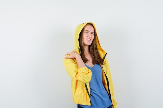 Giovane donna in t-shirt, giacca che soffre di dolore alla spalla e sembra a disagio, vista frontale.