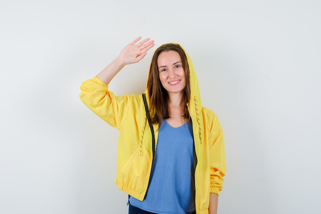 Young lady in t-shirt, jacket waving hand for greeting and looking happy, front view.